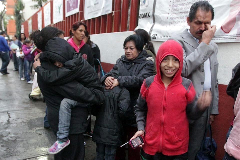 padres con niños en largas filas para tramitar certificado médico