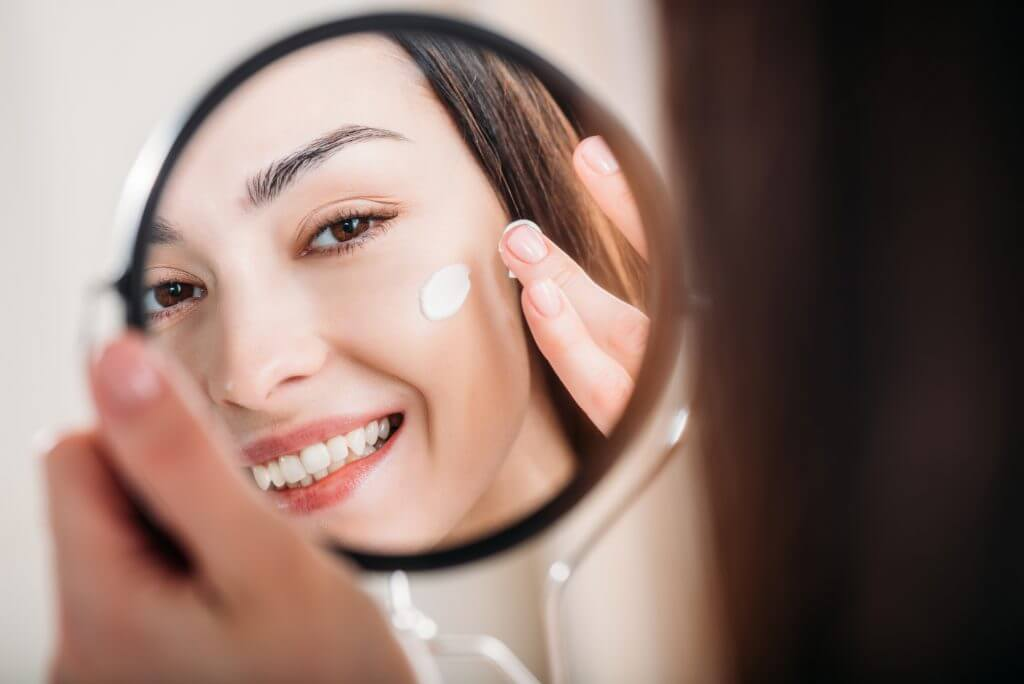 mujer aplicándose crema facial
