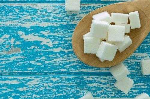 Cubos de azúcar en cuchara de madera