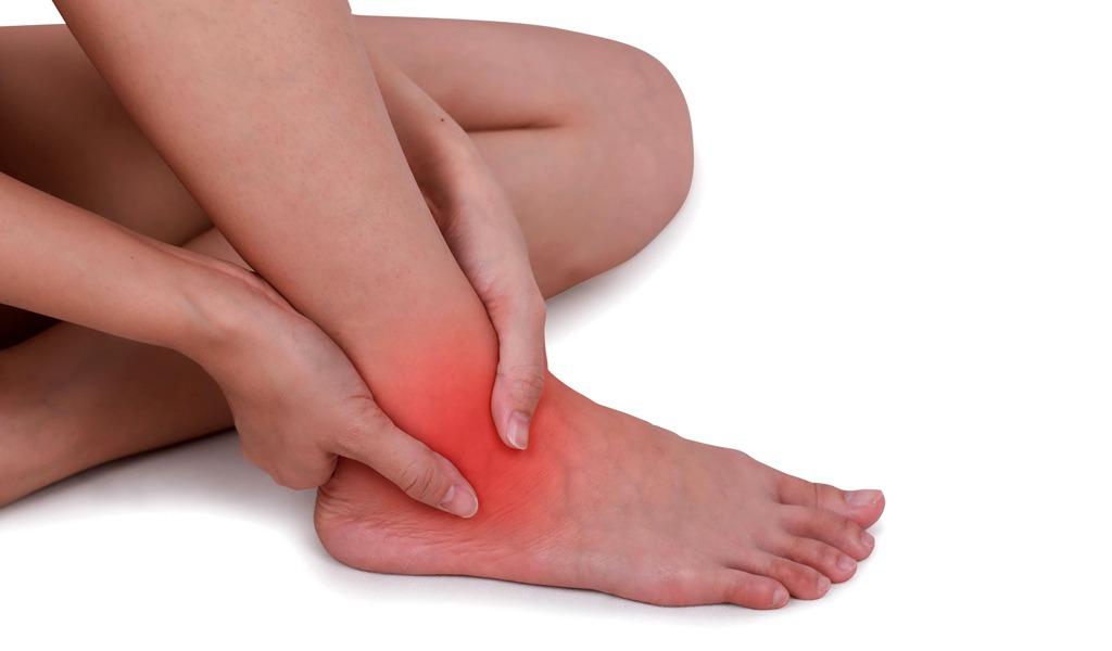 manos al rededor de un tobillo lesionado