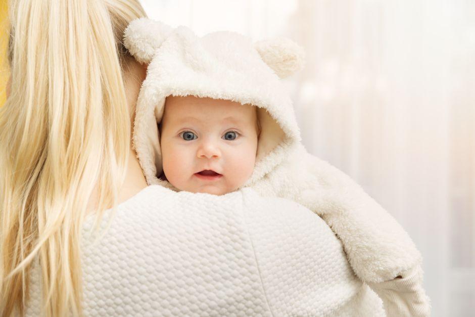 Bebé abrigado en los brazos de su mamá