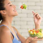 Chica comiendo ensalada para mejorar la digestión