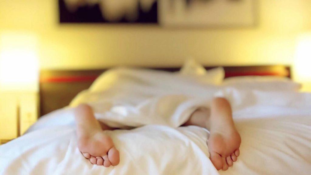 Persona con pies salidos de la cama