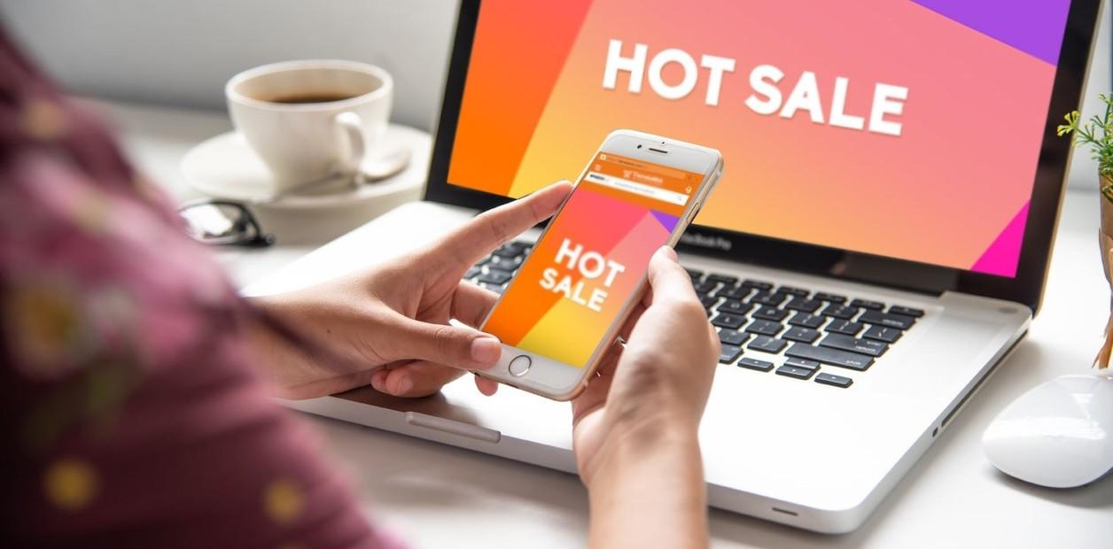 Persona viendo qué es Hot Sale en su celular y en la computadora