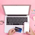 Escritorio de una chica con tarjeta de crédito a la mano