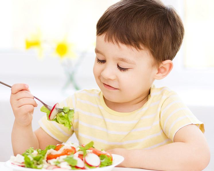 Niño comiendo una ensalada