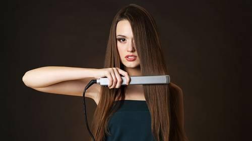 Chica con plancha en su cabello sano