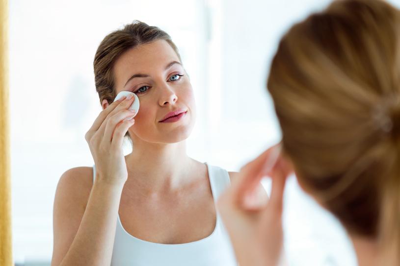 Chica limpiando su piel con acné