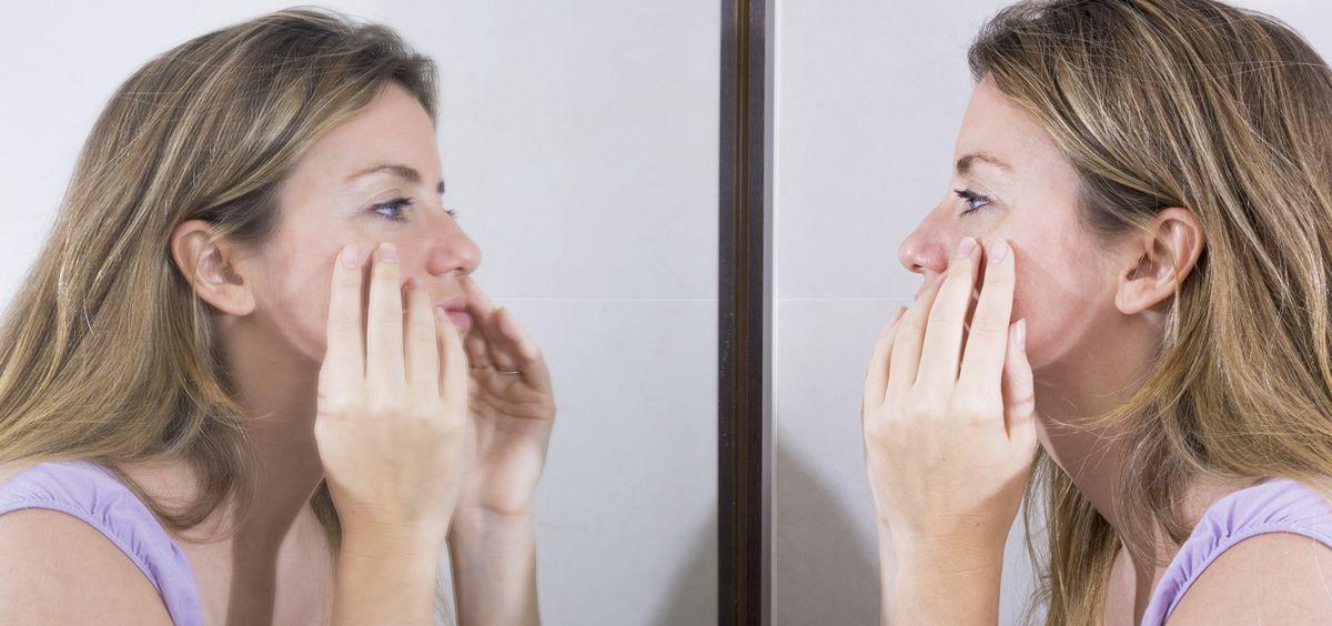 Mujer exprimiendo un barro de su cara